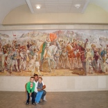 My husband and our boys inside, in front of a massive painting depicting Albanians.